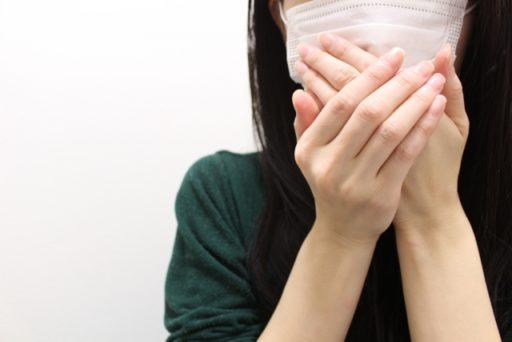 自分の口臭が気になり口を覆う女性