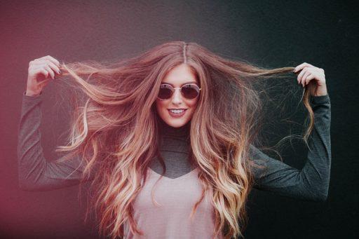 髪を触るロングヘアの女性